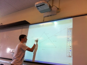 Brendan Mokler, a freshmen at AHS, shows his work for a math problem on the new class Epson Projector. These projectors, complete with sensor pens, have been installed into almost every classroom in the high school. (Photo by Conor Meehan)