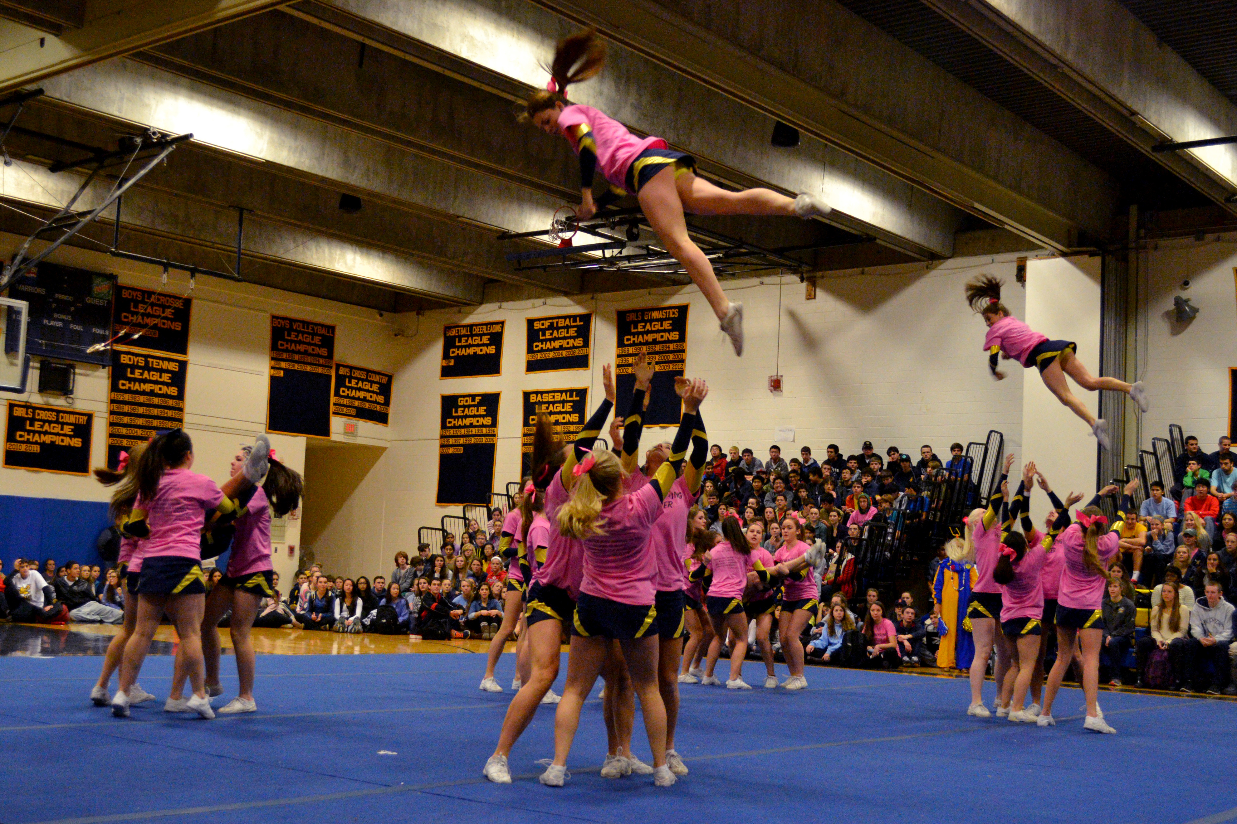 The varsity cheerleaders take to the air to entertain the crowd