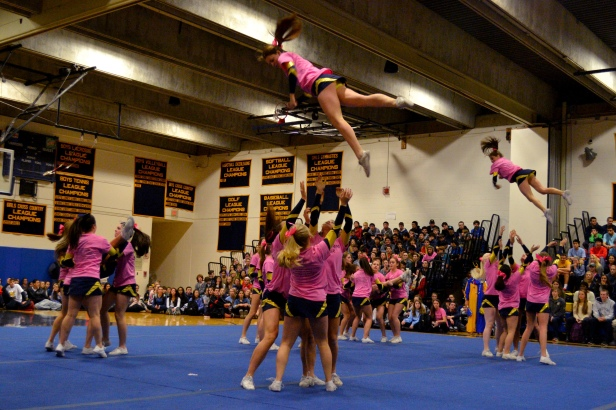 The varsity cheerleaders take to the air to entertain the crowd.