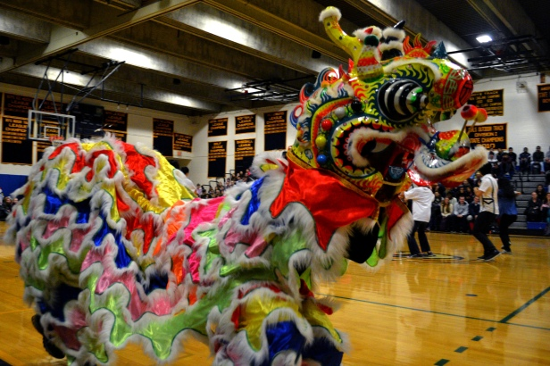 A Chinese dragon (manned by James Lee and Nathan Oh, both seniors) runs around in front of the crowd.