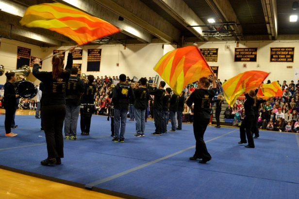 The marching band performs their song during the pep rally, accompanied by the color guard.