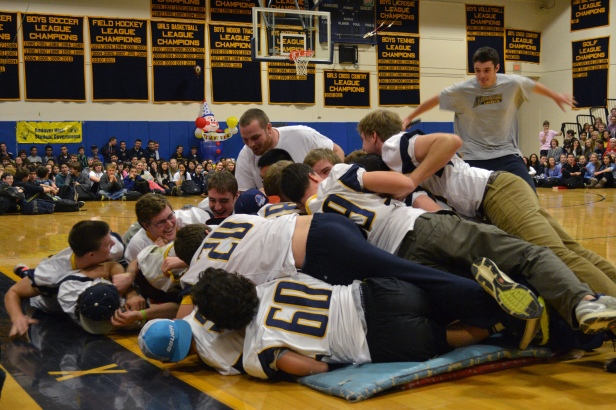 Seniors on the football team pig-pile on senior Kenny Doherty, who wore a Central Catholic t-shirt to get the school pumped for their game against them.